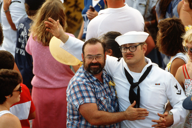 A Sailor from the guided missile frigate USS STARK (FFG 31) is hugged by his father as he waves to other family members upon the STARK's return to its home port.  The STARK has just completed sea trials that followed a stay at the Ingalls Shipbuilding facility in Pascagoula, Mississippi, for repairs to the extensive damage caused by two Iraqi-launched Exocet anti-ship missiles that struck the ship while it was on patrol in the Persian Gulf in May 1987, killing 37 crewmen