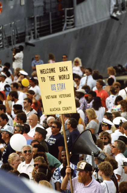 A Vietnam veteran holds a sign as he and a crowd of family and friends of the crew of the guided missile frigate USS STARK (FFG 31) welcome the ship back to its home port.  The STARK has just completed sea trials that followed a stay at the Ingalls Shipbuilding facility in Pascagoula, Mississippi, for repairs to the extensive damage caused by two Iraqi-launched Exocet anti-ship missiles that struck the ship while it was on patrol in the Persian Gulf in May 1987, killing 37 crewmen