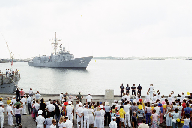 Family and friends of the crew of the guided missile frigate USS STARK (FFG 31) crowd the pier as the STARK returns to its home port.  The STARK has just completed sea trials that followed a stay at the Ingalls Shipbuilding facility in Pascagoula, Mississippi, for repairs to the extensive damage caused by two Iraqi-launched Exocet anti-ship missiles that struck the ship while it was on patrol in the Persian Gulf in May 1987.  Thirty-seven crewmen were killed in the explosion and fires
