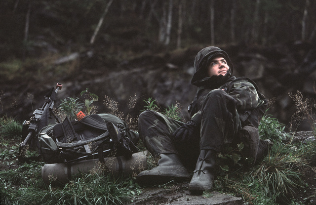 Lance Corporal (LCPL) James McGee watches a helicopter fly over his position along Highway 6 during Exercise TEAMWORK'88