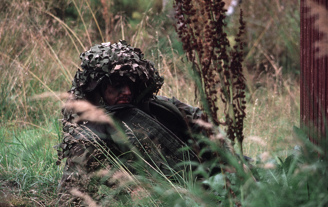 Lance Corporal (LCPL) Richard Armstrong, Co. G, 2nd Battalion, 1ST Platoon, 8th Marines, uses camouflage to evade opposing forces during Exercise TEAMWORK'88