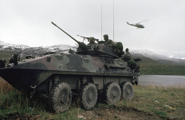 Lieutenant (LT) Scott Bamonte, Lance Corporal (LCPL) Roderick Davis and Corporal (CPL) Thomas Camp take up their position in a 2nd Battalion light armored command and control vehicle (LAV25) during Exercise TEAMWORK'88.  A UH-1N Iroquois command and control helicopter is visible overhead