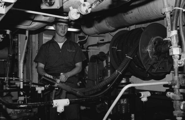 PETTY Officer 2nd Class (PO2) Eric M. Ford, a damage controlman, maintains firefighting equipment in one of the engineering spaces aboard the destroyer USS INGERSOLL (DD 990)