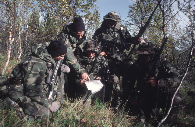 Snipers from Weapons Company 125 consult a map during Exercise TEAMWORK'88. Pictured, from left to right, are: Lance Corporal (LCPL) Stephen Little, Sergeant (SGT) Duane Libby, SGT Steven Roy, LCPL Matthew Sabasteanski and LCPL Raymond Castonguay