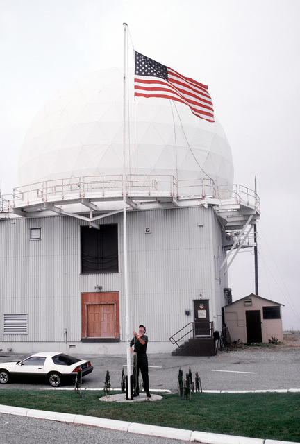 STAFF SGT. Paul Belhumeur raises the flag at the end of his night shift at the San Pedro Joint Surveillance System site. The system, operated by the Air Force and maintained by the FAA, detects unauthorized aircraft and manages air traffic control