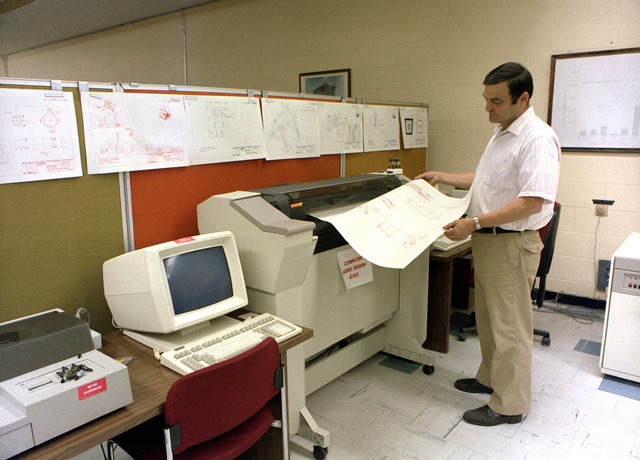 An engineer monitors a printout as he uses the Computer Aided Design (CAD) system to develop the mount system for the tail section of the B-1 bomber