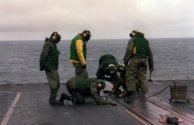 Flighter deck crewmen service a catapult track aboard the aircraft carrier USS Forrestal (CV-59) during exercise Team Work '88