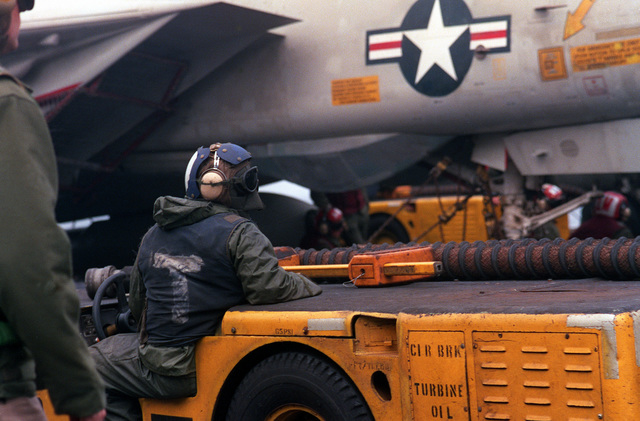 A flight deck crewman positions an MD-3A tow tractor beside an F-14A Tomcat aircraft on the flight deck of the aircraft carrier USS FORRESTAL (CV-59) during exercise Team Work '88