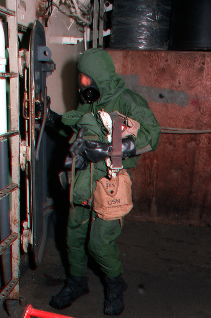 A crewman wearing nuclear-biological-chemical warfare gear opens a water-tight door to investigate a compartment aboard the aircraft carrier USS FORRESTAL (CV-59) during exercise Team Work '88