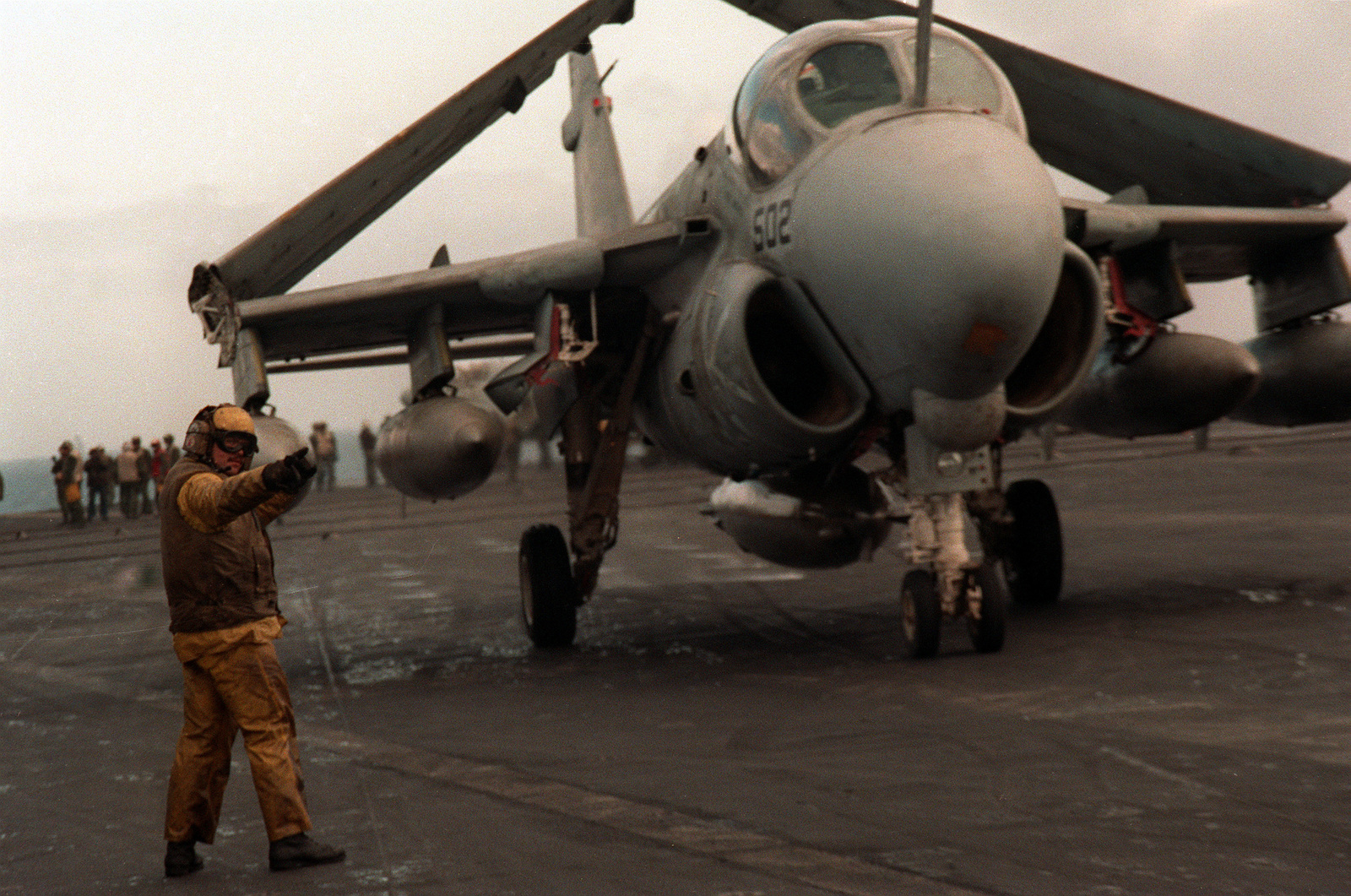 A flight deck crewman guides an A-6E Intruder aircraft from its parking space on the flight deck of the aircraft carrier USS FORRESTAL (CV-59) during exercise Team Work '88