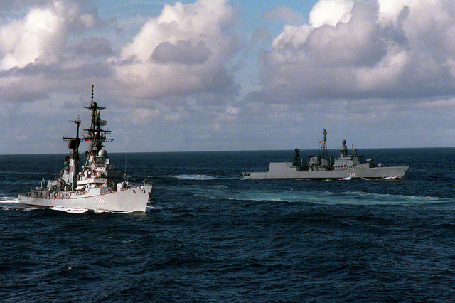A starboard beam view of the West German frigate FGS Lutjens (D-185), foreground, and the West German frigate FGS Niedersachsen (F-208) underway during exercise Team Work '88