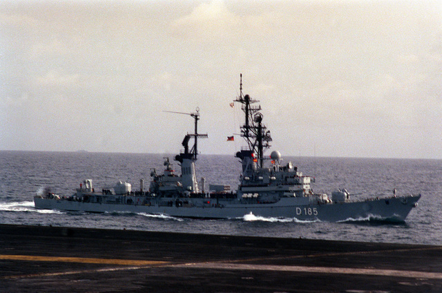 A starboard bow view of the West German destroyer FGS Lutjens (D-185) underway alongside the aircraft carrier USS FORRESTAL (CV-59) during exercise Team Work '88