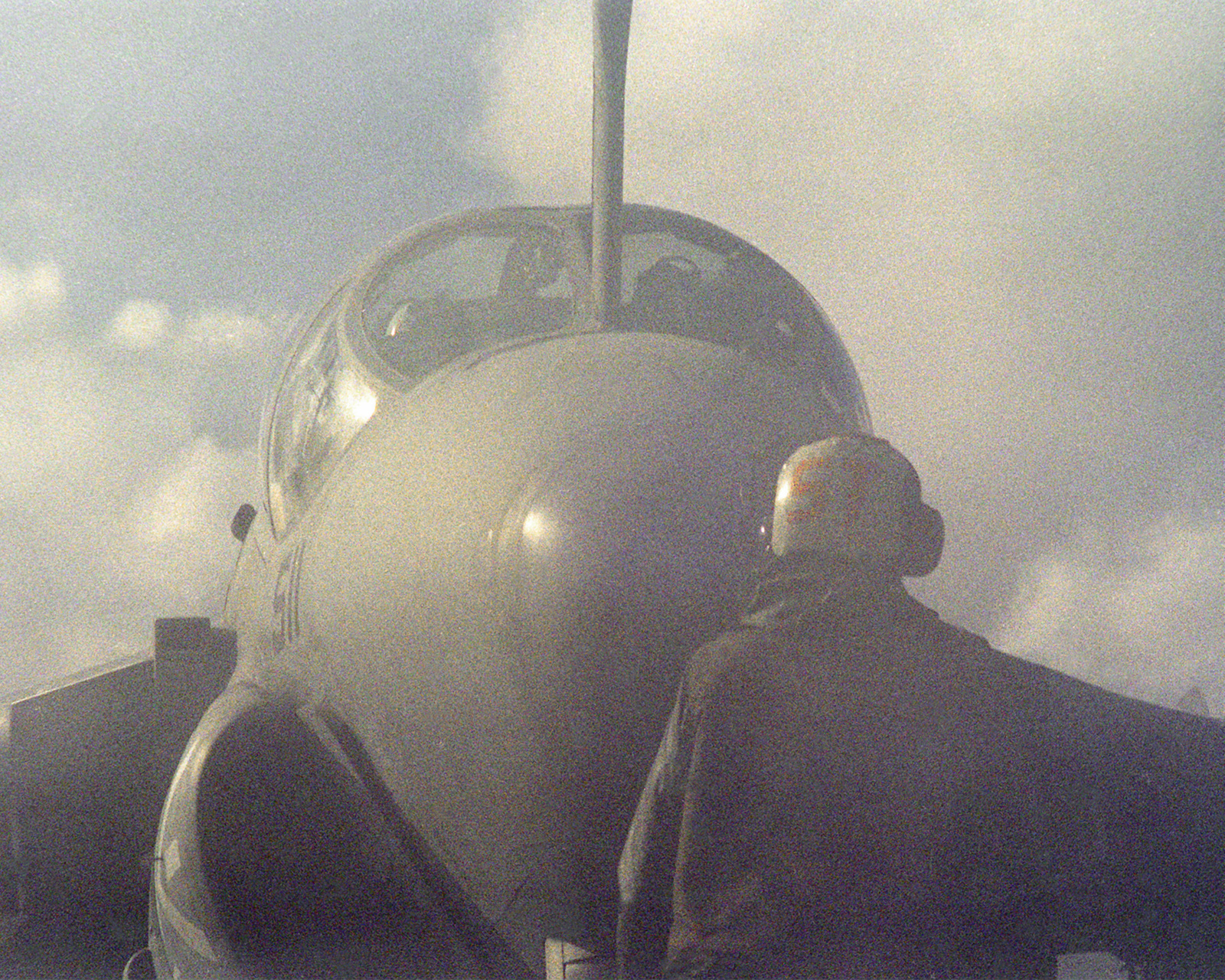 Steam from a catapult obscures a plane handler and the A-6E Intruder aircraft that he is guiding across the flight deck of the aircraft carrier USS FORRESTAL (CV-59) during the allied forces exercise Team Work '88