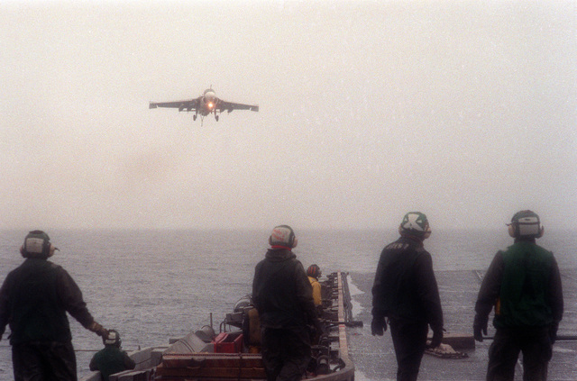 Flight deck crewmen watch as a KA-6D Intruder aircraft descends through a heavy fog to land aboard the aircraft carrier USS FORRESTAL (CV-59) during the allied forces exercise Team Work '88