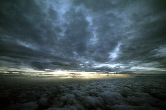 A sunrise over the Gulf of Mexico is sandwiched between two layers of clouds pushed by the advancing Hurricane Gilbert, as seen from a WC-130H Hercules aircraft from the 53rd Weather Reconnaissance Squadron