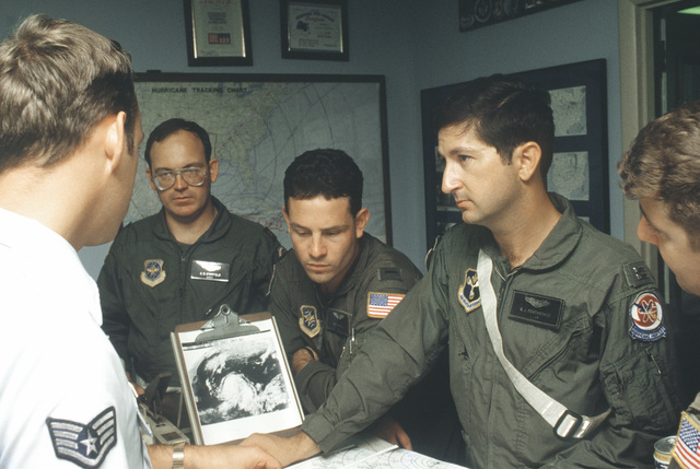 A WC-130H Hercules aircraft crew from the 53rd Weather Reconnaissance Squadron is given a briefing on the weather aloft as Hurricane Gilbert advances across the Gulf of Mexico. The crew will fly their aircraft into the hurricane Gilbert advances across th