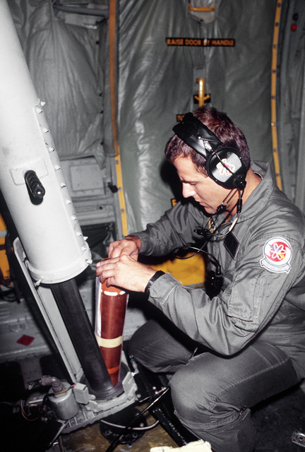 "Aboard a WC-130H Hercules aircraft of the 53rd Weather Reconnaissance Squadron, AIRMAN 1ST Class Timothy Fields places a wind sonde into ""the tube,"" from which it will be dropped into Hurricane Gilbert to relay meteorological data back to the aircraft"