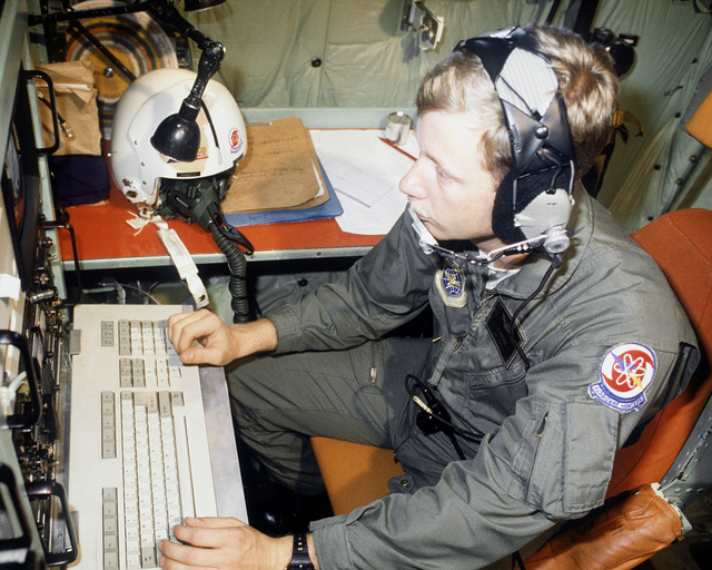 Aboard a WC-130H Hercules aircraft, SGT James Maddox, a drop wind sonde operator with the 53rd Weather Reconnaissance Squadron, monitors the information being displayed on the computer terminal at his station as the aircraft orbits the eye of Hurricane Gi