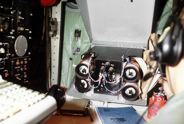"""Four drop wind sondes are calibrated in an """"incubator"""" aboard a WC-130H Hercules aircraft before being dropped into Hurricane Gilbert to relay information on wind speed, dew point and barometric pressure back to the aircraft. The aircraft from the 53rd We"""