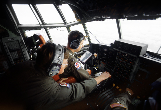 Inside the cockpit of a WC-130H Hercules aircraft, flight engineer TSGT Robert Bruhl adjusts the throttle as the aircraft's pilot, CPT carl Blatz, checks over some navigation data cards. The Hercules and its crew from the 53rd Weather Reconnaissance Squad