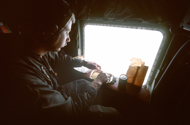 SGT James Maddox, the drop wind sonde operator aboard a WC-130H Hercules aircraft, takes a moment to eat his lunch as the aircraft orbits the eye of Hurricane Gilbert, gathering meteorological data. The aircraft is assigned Keesler Air Force Base, Mississ