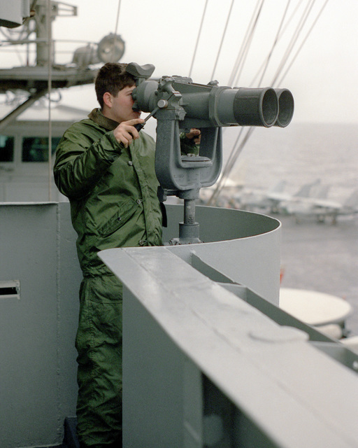 A lookout peers through a pair of ship's binoculars while standing watch aboard the aircraft carrier USS FORRESTAL (CV-59) during the allied forces exercise Team Work '88
