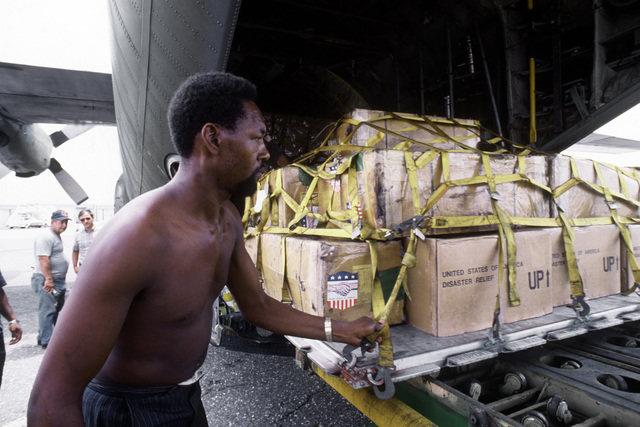 A Jamaican helps offload disaster relief supplies from a C-130 Hercules aircraft of the 50th Tactical Airlift Squadron. The supplies, furnished by the U.S., will be used to aid Jamaicas affected by Hurricane Gilbert, a powerful storm that devastated much