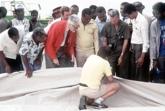 A State Department disaster relief specialist displays a tarpaulin that is among the nearly 14 tons of U.S.-provided supplies flown in earlier in the day to help Jamaica recover from the effect of Hurricane Gilbert. Standing third from left is Michael Sot