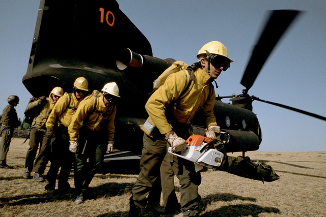 Civilian firefighters from the Mammoth Hot Springs firefighters'camp carry their equipment from an Army CH-47 Chinook helicopter of the 214th Aviation Regiment near the fire lines at Lodgepole as part of the joint military/civilian effort to battle the wi