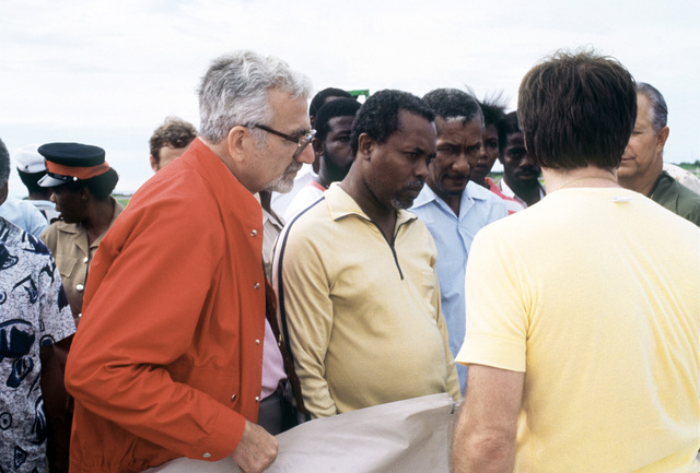Michael Sotirhas, left, the U.S. ambassador to Jamaica, listens as a State Department disaster relief expert explains the features of a plastic tarpaulin. The tarpaulin is among the nearly 14 tons of U.S.-provided supplies that were flown in earlier in th