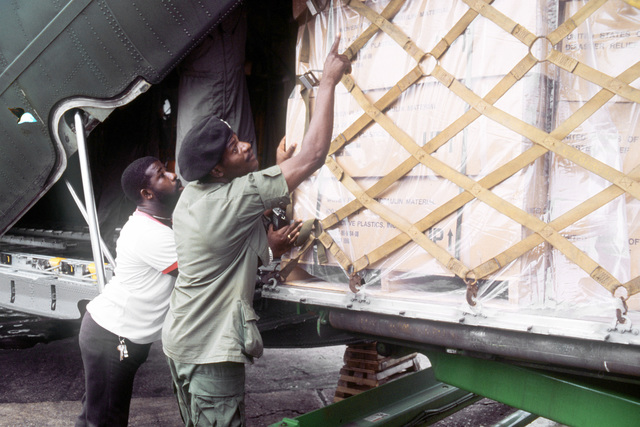 Two Jamaicans help to unload a pallet of plastic tarpaulins from a C-130 Hercules aircraft of the 50th Tactical Airlift Squadron. The supplies were furnished by the U.S. to help Jamaica deal with the devastation caused by Hurricane Gilbert, which hit the