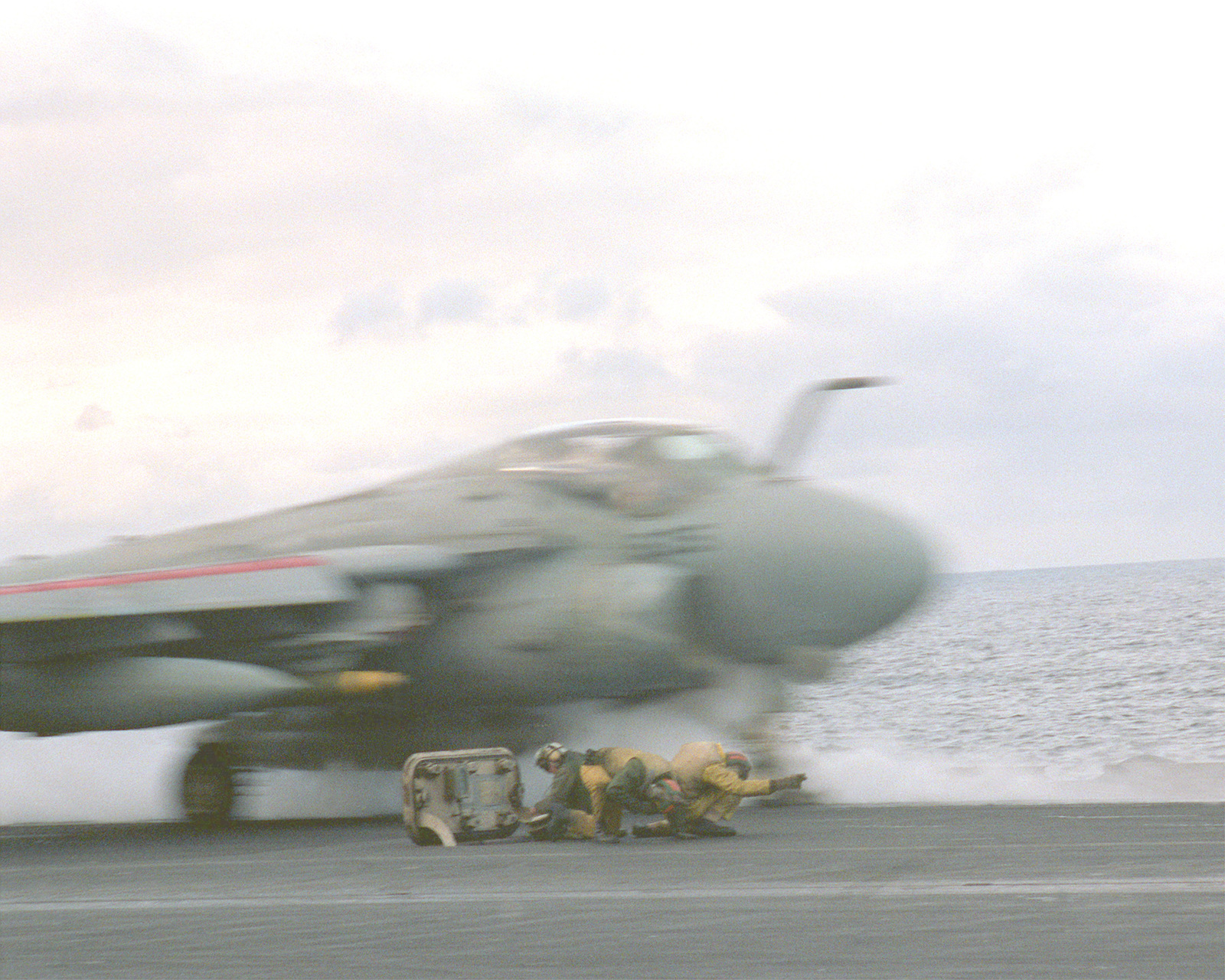 A catapult officer and his crew keep their heads down as an A-6E Intruder aircraft is launched from the flight deck of the aircraft carrier USS FORRESTAL (CV-59) during the allied forces exercise Team Work '88
