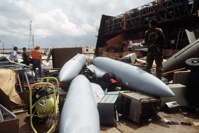Members of the Standarized Tanks, Racks, Adaptors, Pylon, and Packages (STRAPP) team search through the rubble to salvage items in the aftermath of Hurricane Gilbert which caused considerable damage at the San Antonio Air Logistics Center.  Fuel tanks for