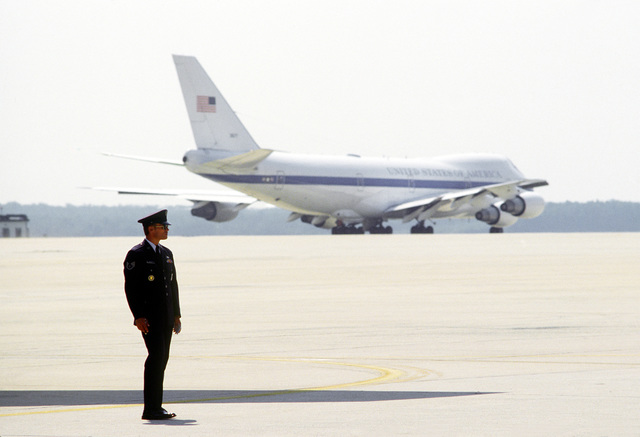 An unidentified airman stands by on the flight line. A Boeing 747 aircraft is parked on the tarmac in the background. The current Boeing 707 aircraft will be replaced by the 747 as Air Force One by early 1989