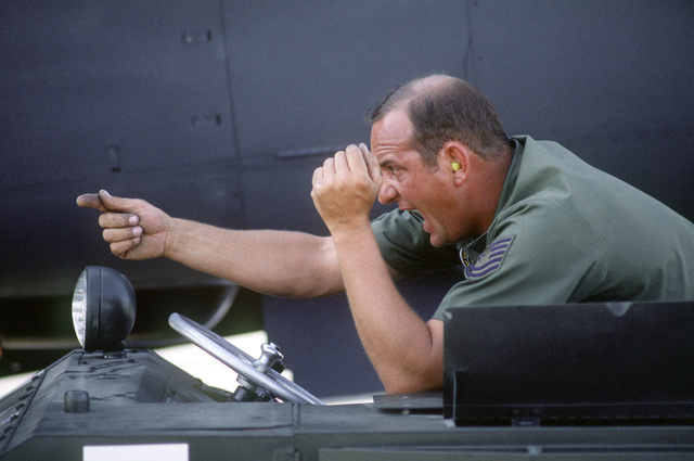 TECH. SGT. John Mitchell directs weapon loading on an A-7 Corsair II aircraft during Gunsmoke '87, an Air Force-wide tactical gunnery and bombing competition sponsored by the Tactical Air Command and hosted by the Tactical Fighter Weapons Center at Nellis