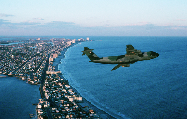 A C-5B Galaxy aircraft assigned to the 436th Military Airlift Wing is flown along the coastline by members of the 512th Military Airlift Wing, Air Force Reserve