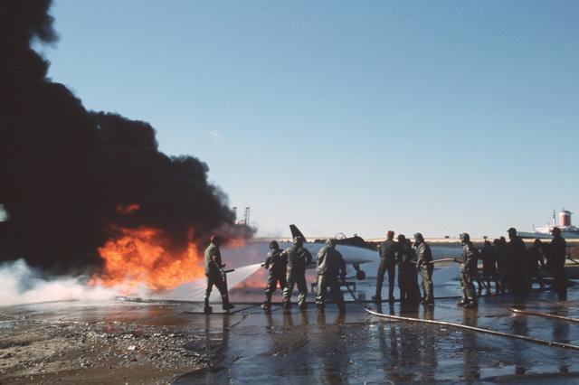 A student hose team battles a blaze engulfing a simulated aircraft during an exercise at the Norfolk Fleet Training Center Firefighting School