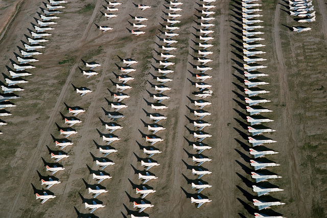An aerial view of some of the more than 2,500 aircraft stored at the Aerospace Maintenance and Regeneration Center. At left and right are rows of F-106 Delta Dart aircraft: between them are four rows of T-39 Sabreliner aircraft. At upper right are several