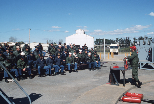 An instructor lectures students on the proper use of a fire extinguisher during an exercise at the Norfolk Fleet Training Center Firefighting School