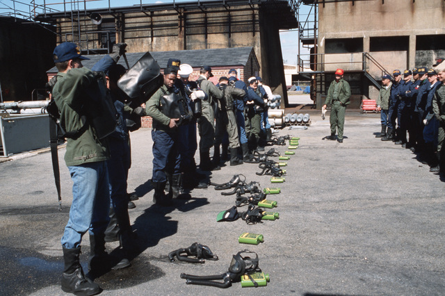 An instructor observes as students adjust their A-4 oxygen breathing apparatus during an exercise at the Norfolk Fleet Training Center Firefighting School