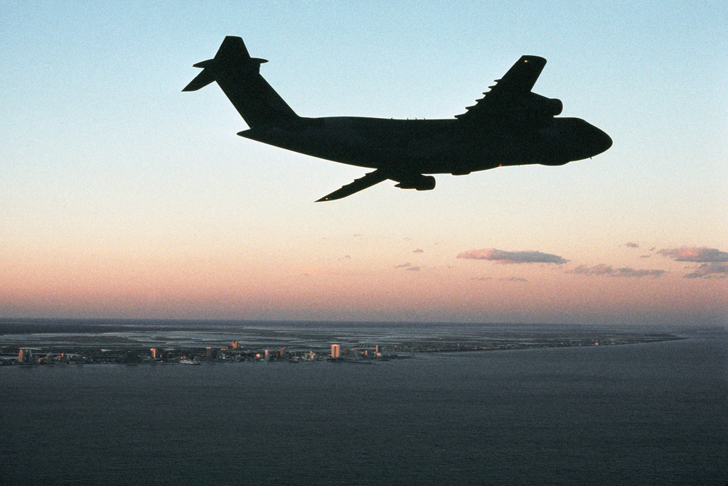 Silhouetted against the sunset, a C-5B Galaxy aircraft assigned to the 436th Military Airlift Wing is flown along the coastline by members of the 512th Military Airlift Wing, Air Force Reserve