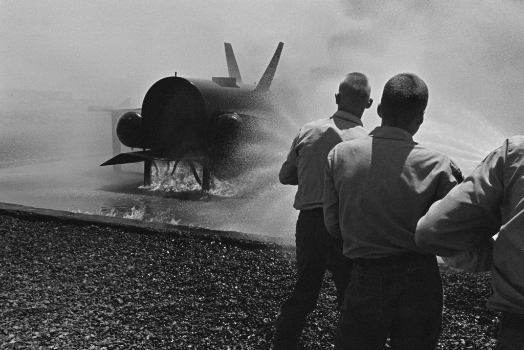 US Naval Sea Cadets battle a fire that was set aboard a mock aircraft during firefighting training