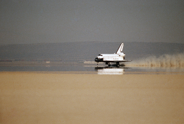 A trail of dust belies the wet appearance of the sun-baked surface of Rogers Dry Lake as the space shuttle orbiter Discovery touches down at the conclusion of Space Transportation System mission 26