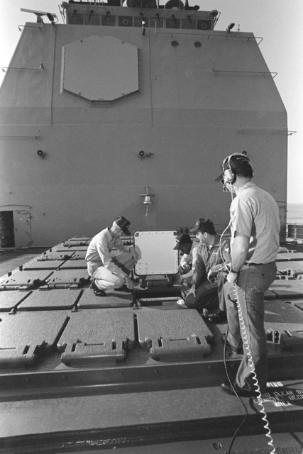 SENIOR CHIEF GUNNER's Mate Raymond E. Smith, left, vertical launch system (VLS) supervisor aboard the guided missile cruiser USS SAN JACINTO (CG 56), listens as GUNNER's Mate Missiles 1ST Class Jack A. Grant, second from right, gives a familiarization lecture on the ship's Mark 41 VLS to GUNNER's Mate Missiles SEAMAN Eric S. Glover, who is squatting beside Grant. GUNNER's Mate Missiles 2nd Class Kip L. Carroll, right, stands safety watch