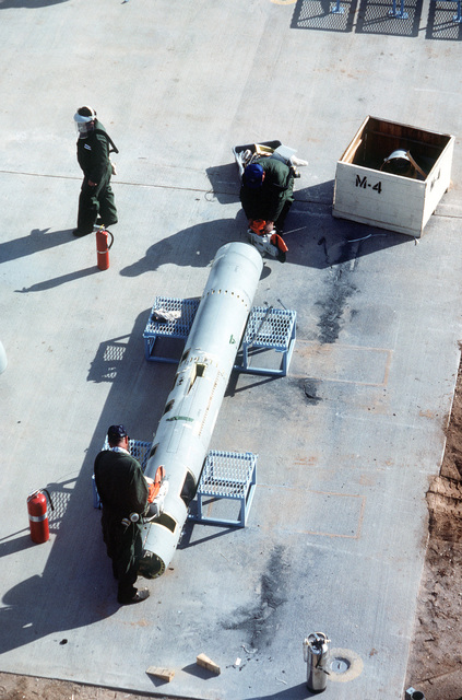 An overhead view of workers at the Aircraft Maintenance and Regeneration Center cutting up a BGM-109G Tomahawk ground launched cruise missile (GLCM).  Forty-one GLCMs and their launch canisters and seven transporter-erector-launchers are being disposed of at the base in the first round of reductions mandated by the Intermediate Range Nuclear Forces Treaty