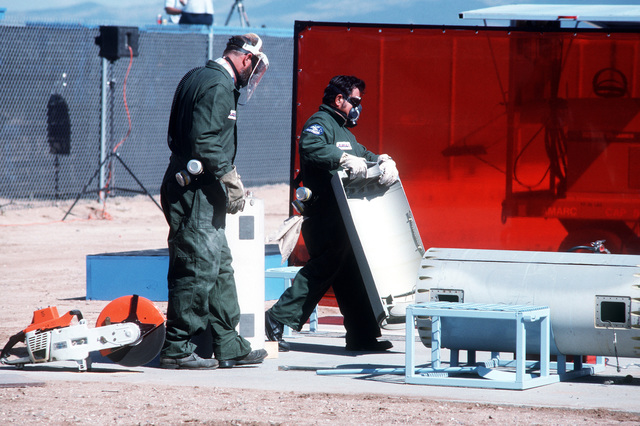 Two employees of the Aircraft Maintenance and Regeneration Center carry away sections of a BGM-109G Tomahawk ground launched cruise missile, the first of 41 that will be destroyed in the initial round of reductions mandated by the Intermediate Range Nuclear Forces Treaty.  Forty-one launch canisters and seven transporter-erector-launchers will also be disposed of in the first round