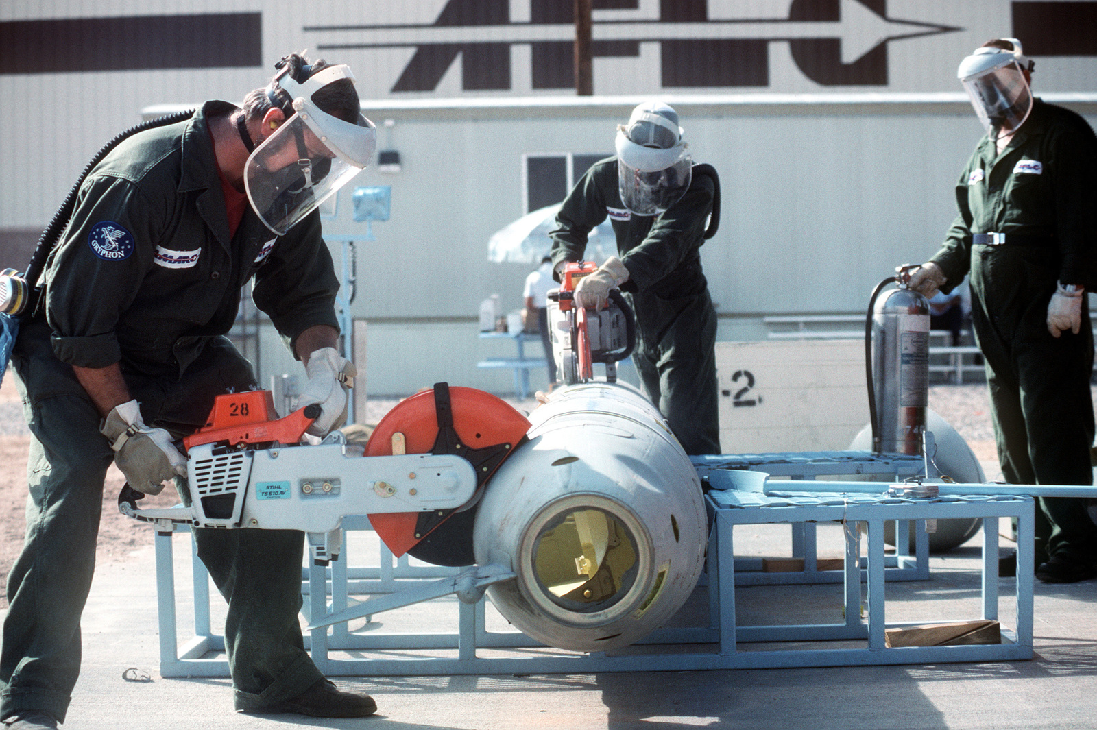 Two employees of the Aircraft Maintenance and Regeneration Center cut up a BGM-109G Tomahawk ground launched cruise missile (GLCM) as a third stands by with a fire extinguisher.  Forty-one GLCMs and their launch canisters and seven transporter-erector-launchers are being disposed of at the base in the first round of reductions mandated by the Intermediate Range Nuclear Forces Treaty