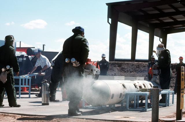 Workers use circular saws to cut into the body of a BGM-109G Tomahawk ground launched cruise missile (GLCM).  Forty-one GLCMs and their launch canisters and seven transporter-erector-launchers are being disposed of at the base in the first round of reductions mandated by the Intermediate Range Nuclear Forces Treaty