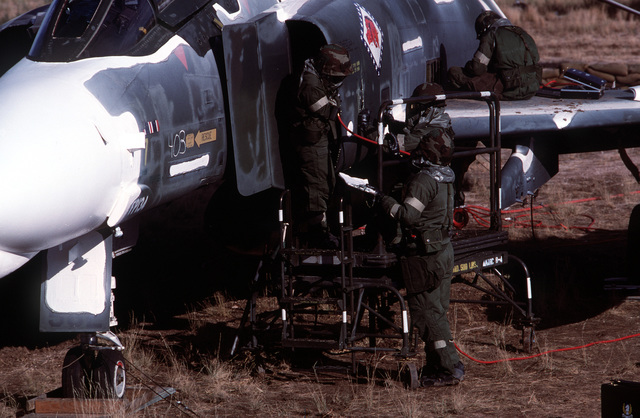Members of a combat logistics support squadron assess damage to an F-4 Phantom II aircraft during an aircraft battle damage repair exercise. The squadron members are equipped with nuclear-biological-chemical warfare gear