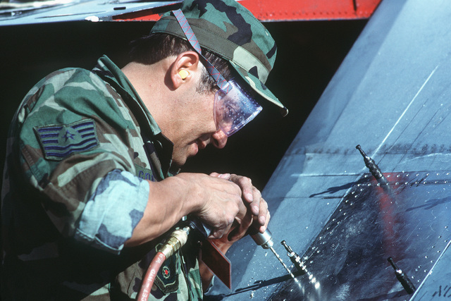 Technical Sergeant (TSGT) Gilberto Gonzales, 404th Combat Logistics Support Squadron, drills holes in a sheet metal patch during an aircraft battle damage repair competition